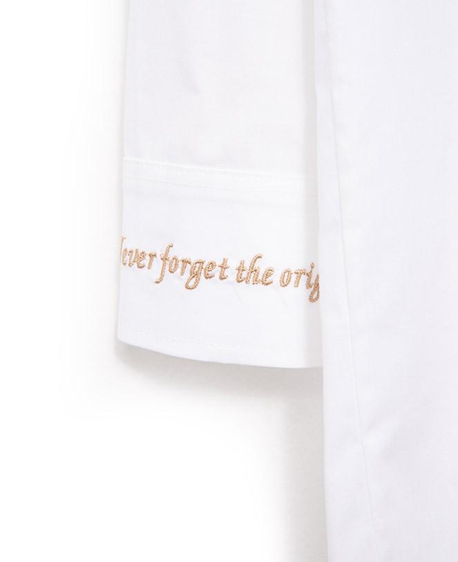 """Vestido Camisero de algodón blanco con canesú y tabla en el centro de la espalda. Cuello camisero. Bolsillo de plastrón en el lado izquierdo de la prenda y en la manga derecha otro de menor tamaño con el escudo de Imiloa en dorado. Cierre en el centro delantero con botones personalizados. Puño con botonadura y el bordado """"Never Forget the Origins"""" en el puño derecho. <h3>COMPOSICIÓN:</h3> 97% Algodón, 3% Spandex Alabama Shop"""