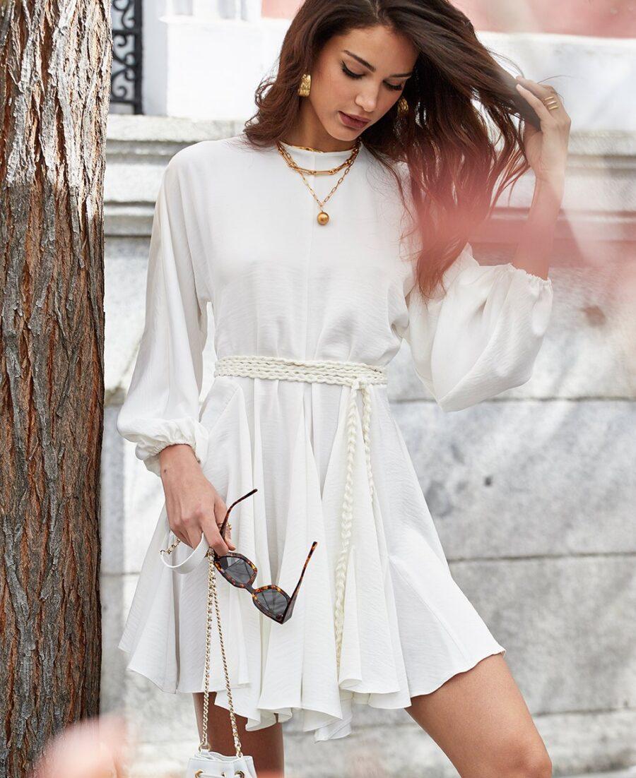 Vestido corto de color blanco roto con cuello redondo y manga murciélago con goma en el puño. Corte central y falda con godets que aportan un volumen extra. Lágrima en la parte trasera con cierre de botón joya. Cinturón de algodón trenzado a modo de detalle.  Alabama Shop